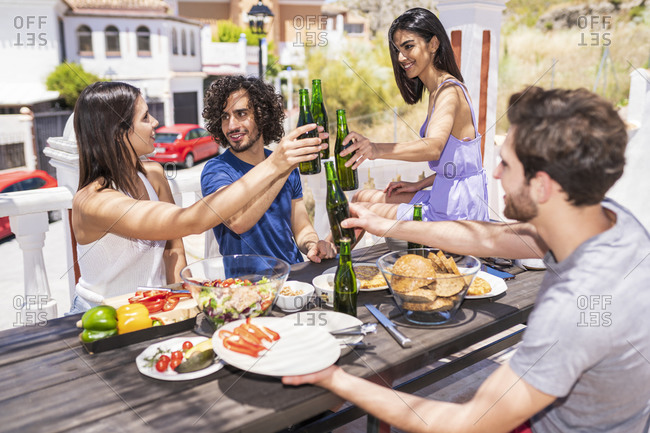 Happy young friends toasting beer bottles while enjoying brunch at building terrace