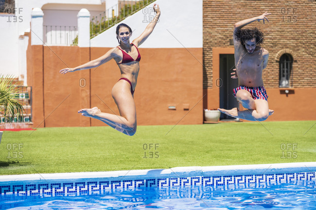 Young multi-ethnic couple diving into swimming pool at back yard on sunny day