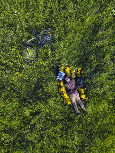 Man lying on grass and using laptop- aerial view