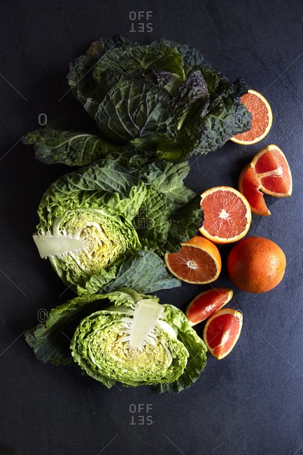 Fresh cabbage head and blood oranges on a dark and moody surface, top view