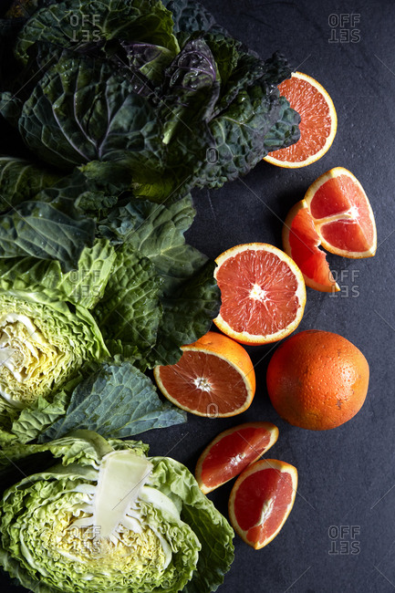 Fresh cabbage head and blood oranges on a dark and moody surface