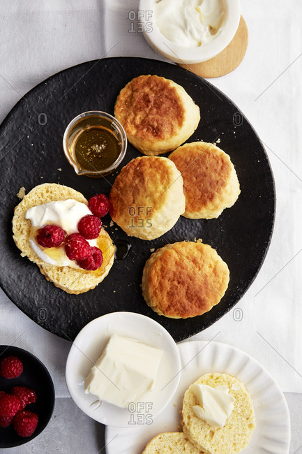 A large plate of scones with honey, raspberries, butter and whipped cream