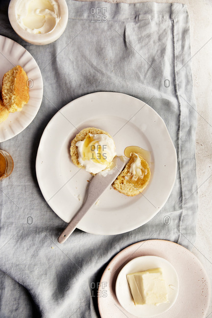 Plate of scones with honey and whipped cream on a linen tablecloth