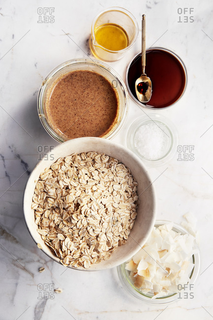 Ingredients for homemade granola laid out on a marble kitchen table