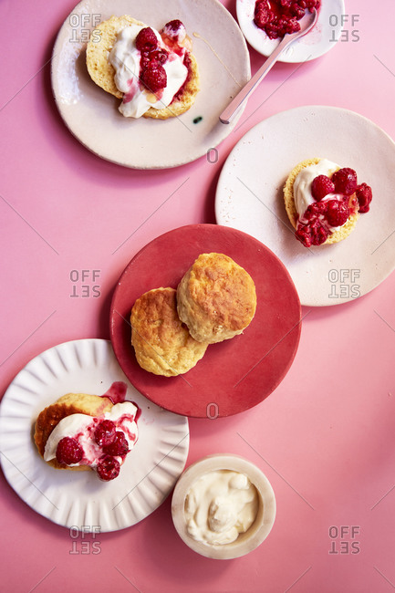 Scones on different plates with cream and raspberry coulis on a pink background