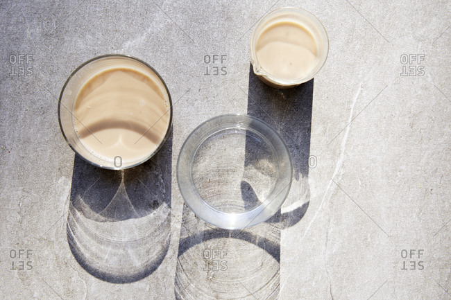 Three glasses in bright light with long shadows, two with nut milk