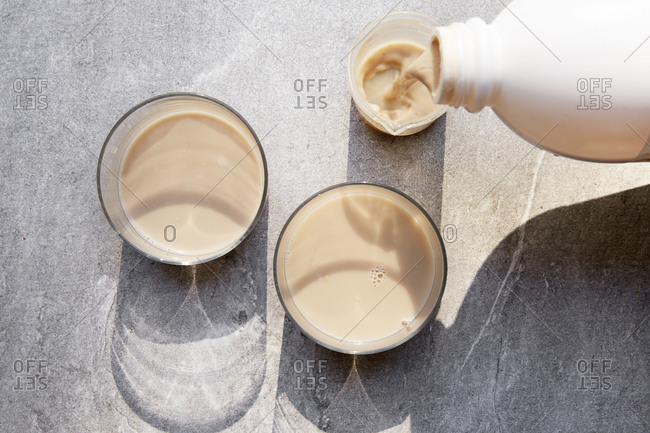 Selection of milk alternatives with milk pouring into a small jug from a top view