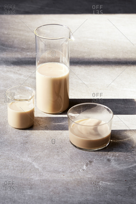 Three glass containers with long shadows filled with milk alternatives