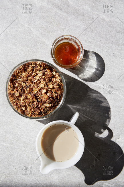 Granola, honey and nut milk on a kitchen counter
