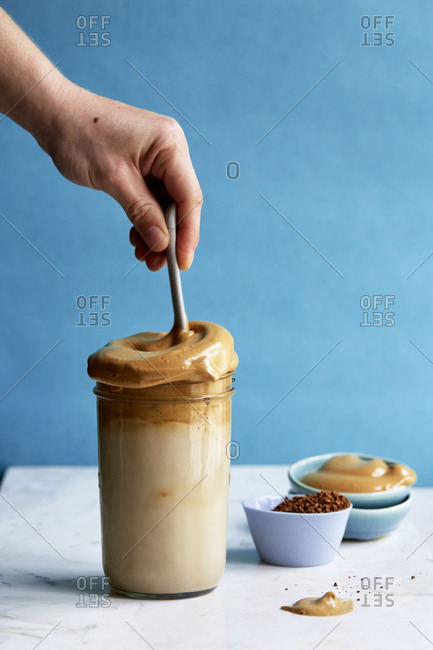 Whipped coffee mixed into a tall glass of milk