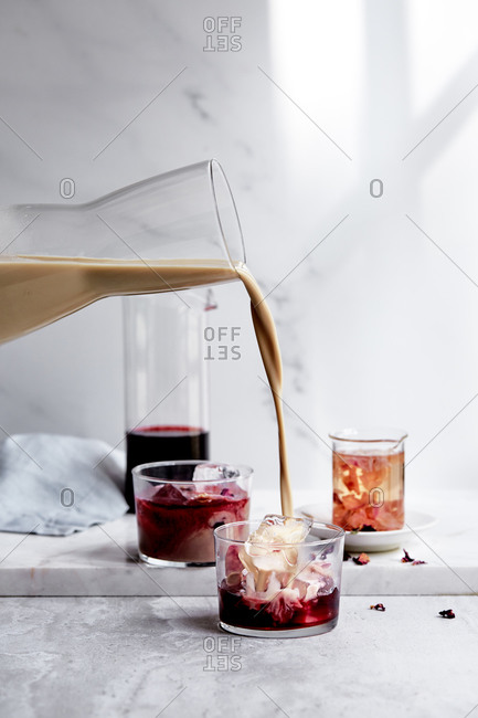Hibiscus and rose ice tea with nut milk being poured into a glass