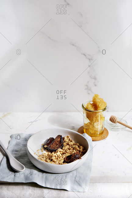 Homemade granola with dried figs, fresh honeycomb and nut milk