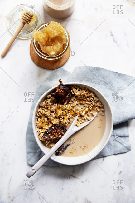 Homemade granola with dried figs, fresh honeycomb and nut milk from above on a marble counter