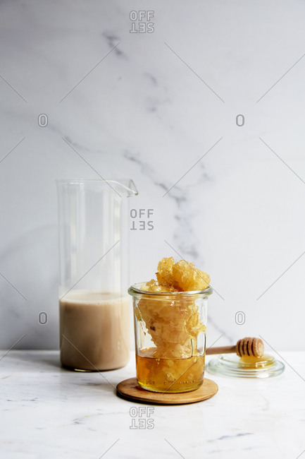 Fresh honeycomb and nut milk on a marble kitchen counter