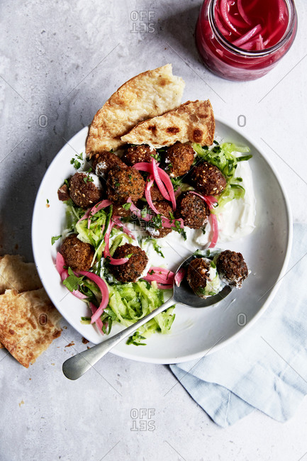 Falafels with pickled red onions, yoghurt and cucumber and naan, top view