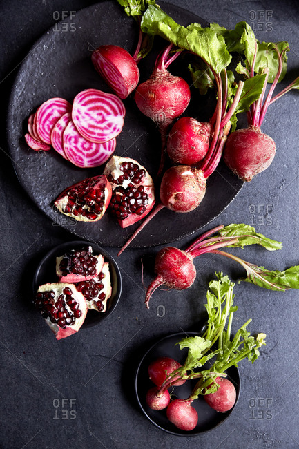 A bunch of candy stripe beetroot and sliced pomegranate on plates