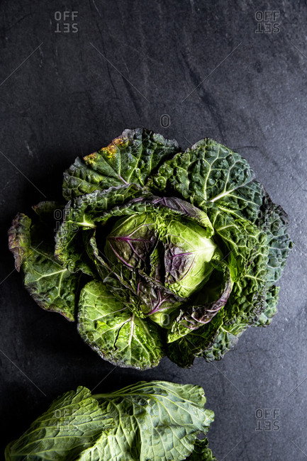Two fresh and whole cabbage head on a moody background