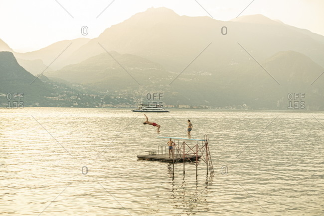 Bellagio, Italy - July 27, 2020: Young adults diving into Lake Como from diving board in the middle of the lake