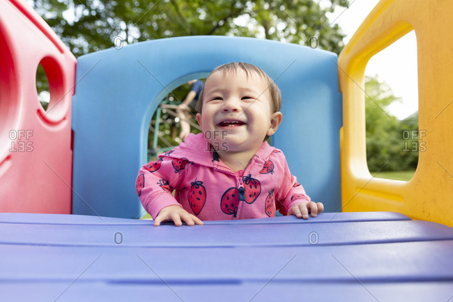 Joyful smiling toddler girl standing in colorful backyard playset