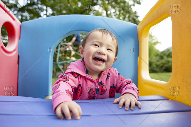 Happy smiling toddler girl plays on colorful jungle gym in backyard
