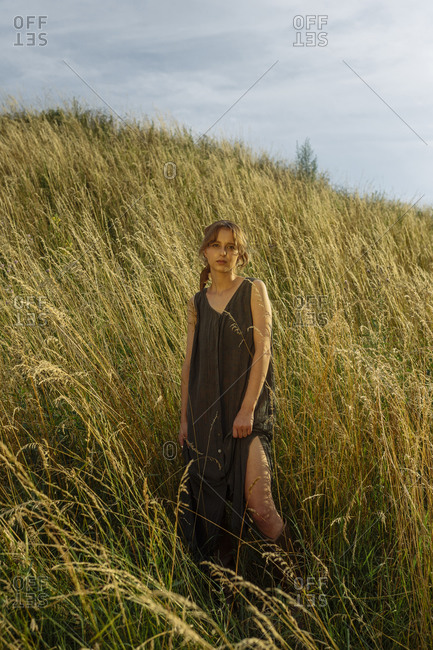 Woman stands on a hill in tall grass