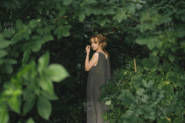 A woman stands in a dress in dense foliage