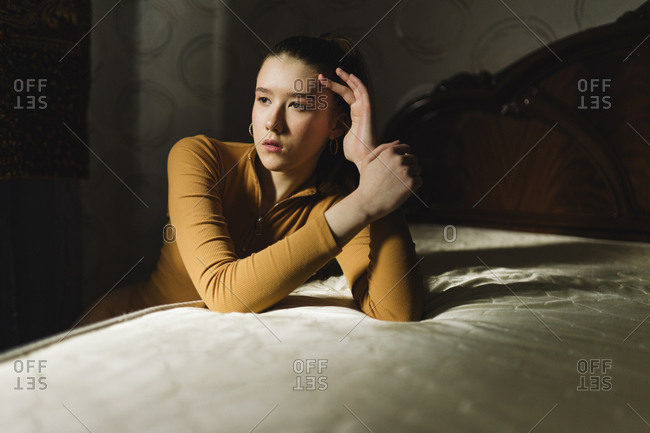 Woman sitting at home near the bed