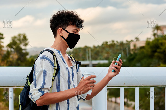 Young afro-haired man with mask is using his mobile on the street