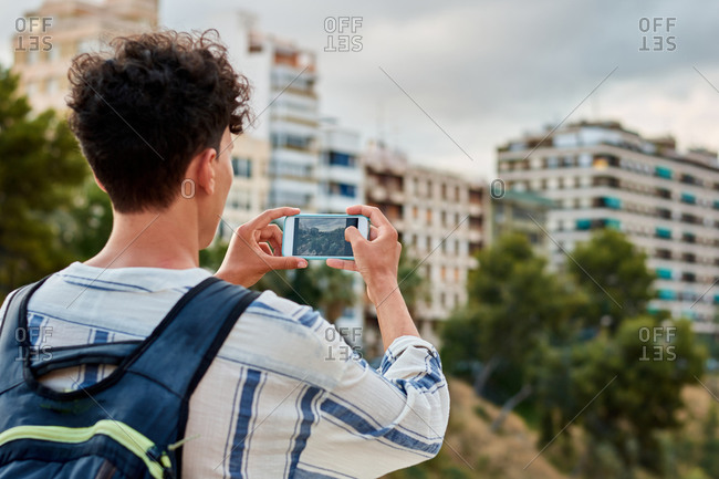 Close-up of a young afro-haired man is taking a photo with his mobile