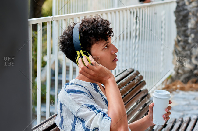 Portrait of a young man with afro hair is listening to music in a park
