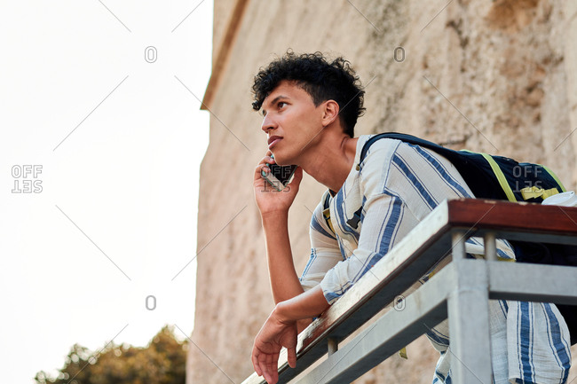 Young man with afro hair is using his smartphone outdoors