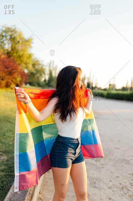 Young woman with the sun on her face with an lgtb flag on her back