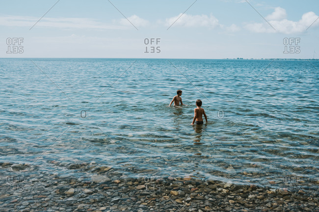Two boys wading in lake ontario on a summer day.