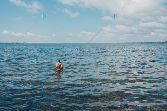 Tween boy wading in lake ontario on a summer day.
