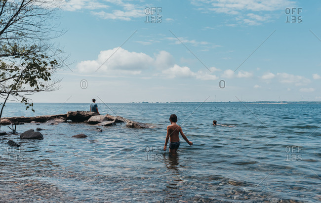 Children wading and swimming in lake ontario on a hot summer day.