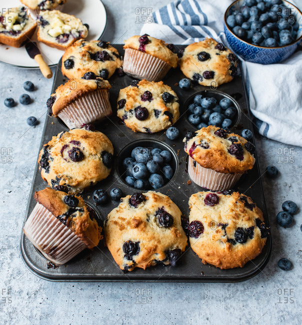 Overhead view of blueberry muffins in baking tin on concrete counter.