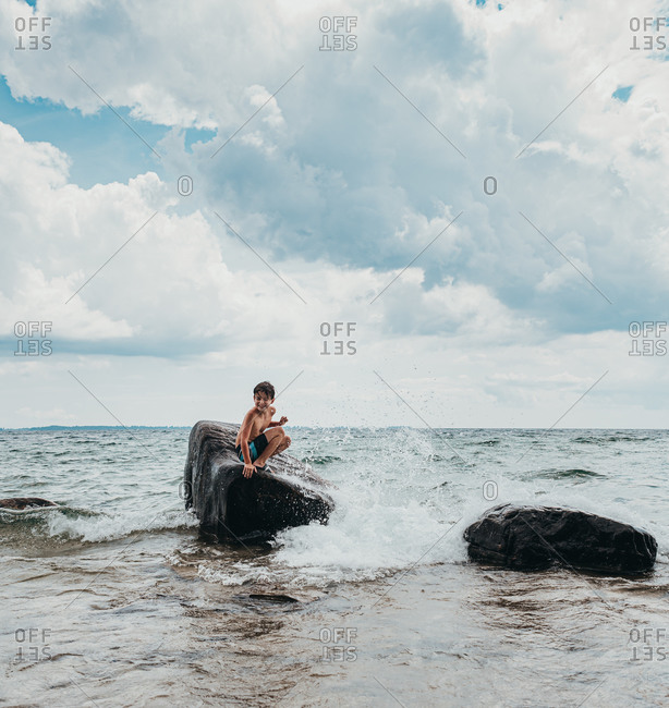 Young boy sitting on big rock in lake getting splashed on summer day.