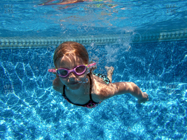 Girl swimming underwater with goggles on