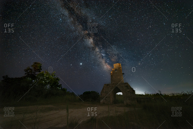 Panorama of an old tower during a starry night with the milky way