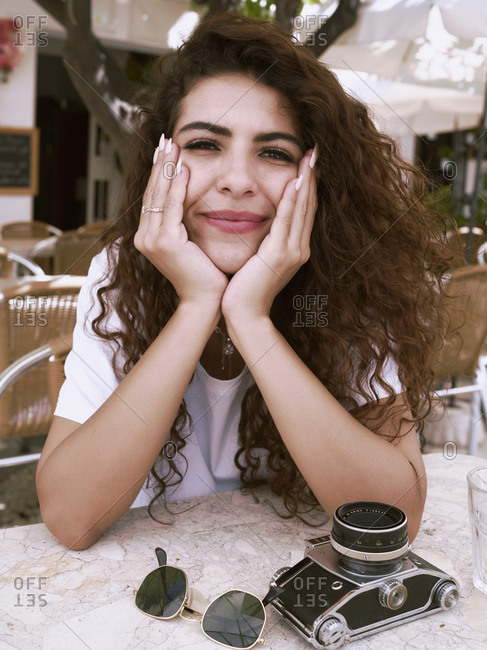 Portrait of a young arabic woman with her hands on her face