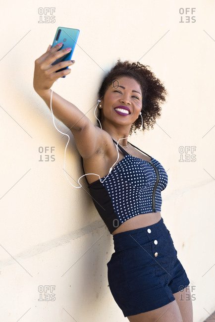Black woman makes a selfie with her cell phone