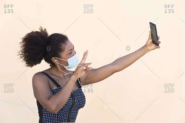 Black woman with a mask makes a selfie with her mobile phone