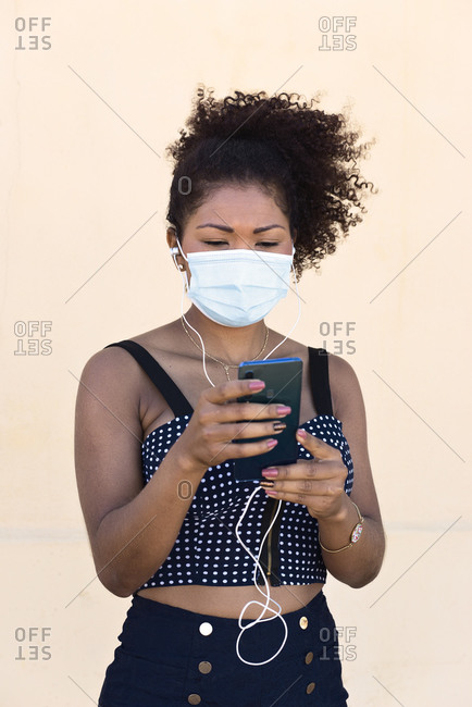 Black woman with mask handles her mobile phone