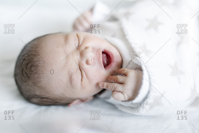 Yawning baby lying in bed