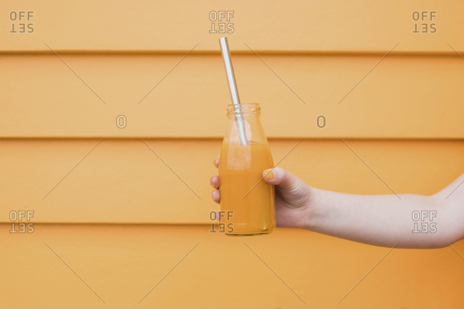 Girl holding glass bottle filled with orange juice with a metal straw