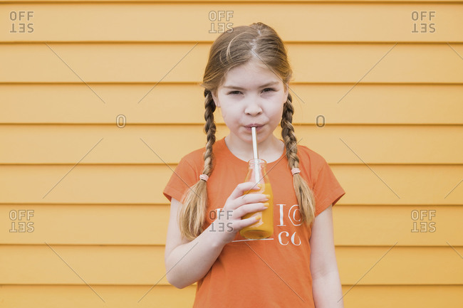 Young girl standing in front of a orange wall drinking juice