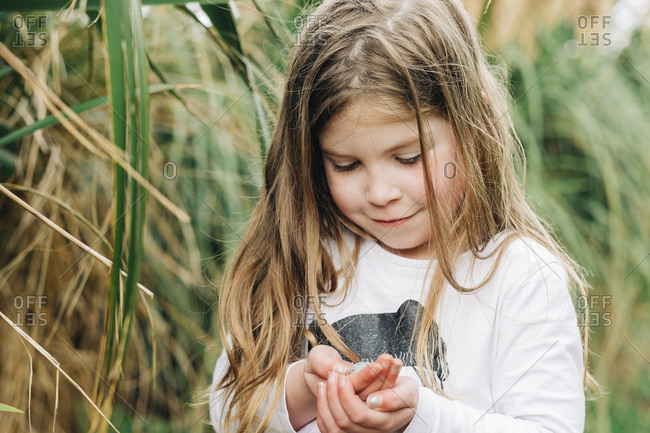 Young girl holding a small birds egg in her hands