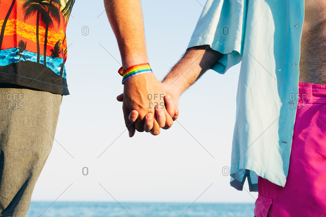 Two men in love holding hands on the beach stock photo.