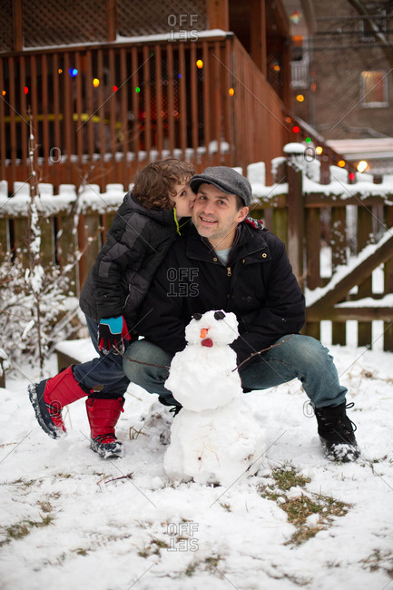 Son kissing his father after they built a snowman in their backyard