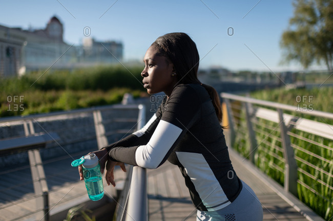 Black runner with water resting on embankment